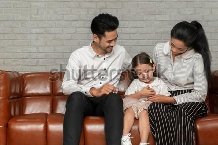 Family planning and Professional Psychological help for family concept. Happy family parent pay attention to the daughter. family, child and home concept - smiling parents and little girl at home.