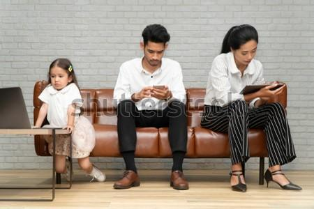 Family psychotherapy and Family planning concept. Professional Psychological help for family. Parent Do not pay attention to the daughter,  Father has Beard holding smartphone, Mom with tablet.