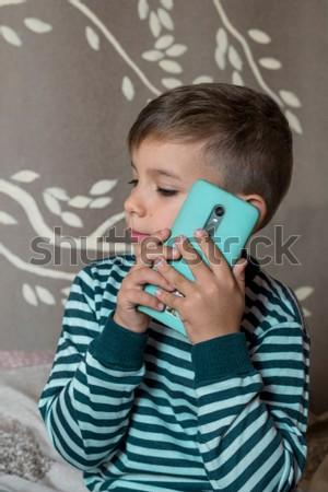 The child calls on the smartphone. The boy in the striped shirt talking on the phone
