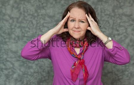 horizontal orientation of a woman in brightly colored business attire with a look of pain while she holds her head with both hands / Business Woman with a Headache