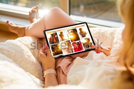 Woman sitting at home and browsing beautiful portrait photos online