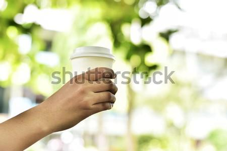 In selective focus of A Cup Of Hot Coffee In Woman Hand Holding Against Blur Green Bokeh Background.Business Travel Outdoor Office Concept.Split tone pinterest,instragram like.Toned With Sun Light.
