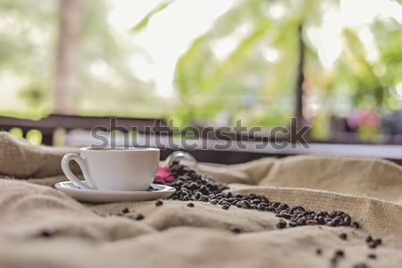 In selective focus of Coffee on Burlap Sack in Open Air Old Kitchen Table. Side view with Copyspace for your text.Split tone instragram like process.with Sun light.